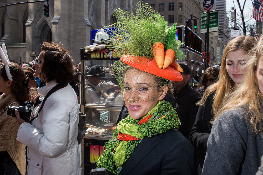 New York, NY, USA-27 March 2016. A woman with a green and orange scarf and a hat with carrots and greens, as if ready to feed the Easter  Bunny, in the annual Easter Bonnet Parade and Festival.