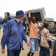 Electronic waste export to Nigeria...Alaba International Market, one of the largest markets for electronic goods in West Africa.  New and old - and a lot of non-working electronic goods such as TVs and computers come in to the market via Lagos harbour from the US, Western Europe and China...Eric Albertsen and his TV.  The TV has travelled all the way from the UK and will now return as evidence of exports breaching the law...The shipment - TV-set originally delivered to municipality-run collecting point in UK for discarded electronic products - was tracked and monitored by Greenpeace using a combination of GPS (Global Positioning System using satellites), GSM (positioning using data from mobile networks to triangulate approximate positions) and an onboard radiofrequency transmitter (used for making triangulations in combination with handheld directional receivers used by team on ground) is placed inside the TV-set.  The TV arrived in Lagos in container no 4629416.