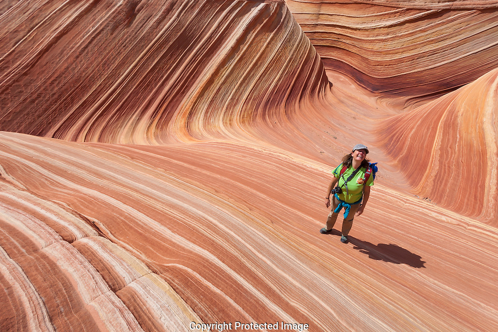 Hiker among the swirled sandstone rock formations at The Wave, Vermilion Cliffs, near Page, Arizona