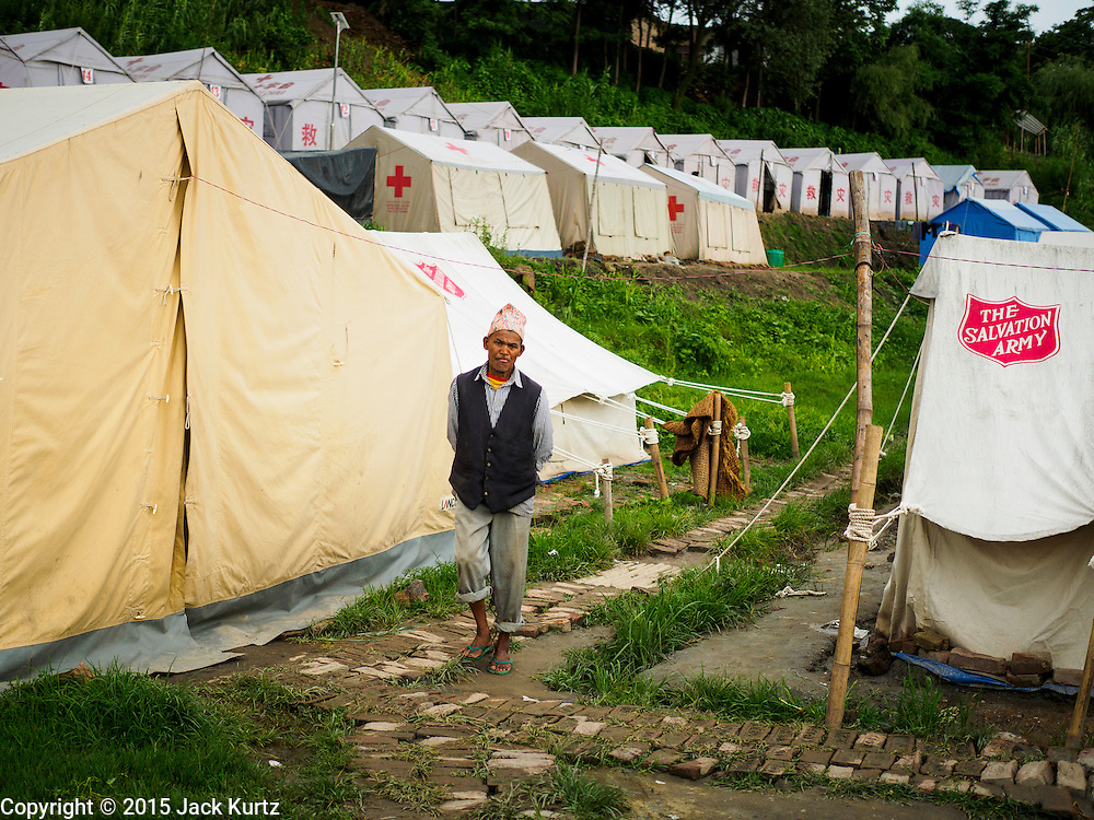 02 AUGUST 2015 - BHAKTAPUR, NEPAL:  A man walks through one of the larger Internal Displaced Persons (IDP) camps on the edge of Bhaktapur. The Nepal Earthquake on April 25, 2015, (also known as the Gorkha earthquake) killed more than 9,000 people and injured more than 23,000. It had a magnitude of 7.8. The epicenter was east of the district of Lamjung, and its hypocenter was at a depth of approximately 15 km (9.3 mi). It was the worst natural disaster to strike Nepal since the 1934 Nepal–Bihar earthquake. The earthquake triggered an avalanche on Mount Everest, killing at least 19. The earthquake also set off an avalanche in the Langtang valley, where 250 people were reported missing. Hundreds of thousands of people were made homeless with entire villages flattened across many districts of the country. Centuries-old buildings were destroyed at UNESCO World Heritage sites in the Kathmandu Valley, including some at the Kathmandu Durbar Square, the Patan Durbar Squar, the Bhaktapur Durbar Square, the Changu Narayan Temple and the Swayambhunath Stupa. Geophysicists and other experts had warned for decades that Nepal was vulnerable to a deadly earthquake, particularly because of its geology, urbanization, and architecture.      PHOTO BY JACK KURTZ