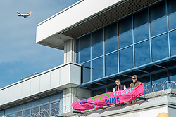 © Licensed to London News Pictures. 10/10/2019. London, UK. Extinction Rebellion protesters occupy the roof of the main entrance to London City Airport as an plane takes off in the distance. Photo credit: Peter Manning/LNP