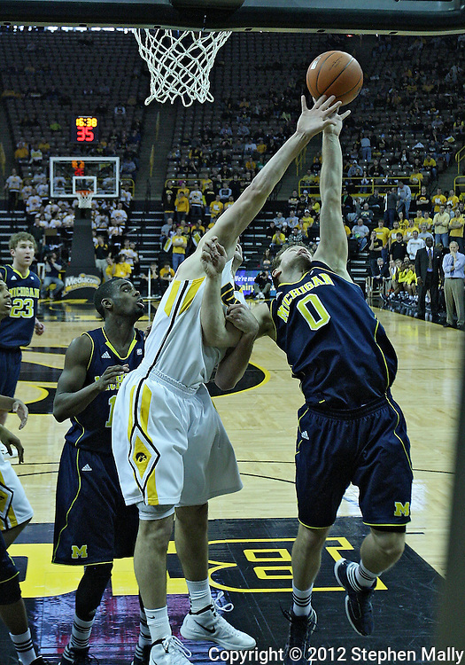 January 14, 2011: Iowa Hawkeyes guard/forward Eric May (25) and Michigan Wolverines guard Zack Novak (0) battle for a rebound during the NCAA basketball game between the Michigan Wolverines and the Iowa Hawkeyes at Carver-Hawkeye Arena in Iowa City, Iowa on Saturday, January 14, 2011. Iowa defeated Michigan 75-59.