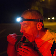Triathlete Paul Parrish has a meal break during the run section of his Arch to Arch triathlon attempt in south London September 13, 2014.
