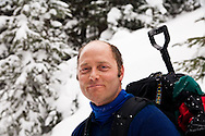 Backcountry skier, Dale Embleton, smiles while touring to Peter Estin hut in a snow storm in Colorado.  Telemark or AT skis with climbing skins are used to climb up steep snow slopes when doing backcountry skiing.