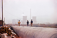 China, Taiyuan, 2008. Kids run along above-ground drainage pipes running parallel to a main coal transport road heading south from Taiyuan.