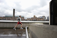 Man joggin along the Thames with the Tate Modern in the background
