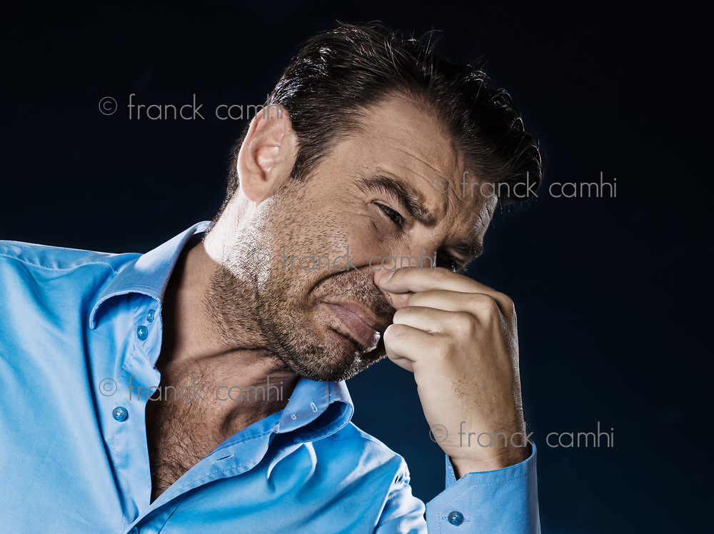 caucasian man unshaven pucker unpleasant smell portrait isolated studio on black background