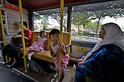 Public bus. Muslim woman and granddaughters.