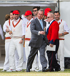 © Licensed to London News Pictures. 19/06/2015. London, UK. NIGEL FARAGE with glass of champaign in hand talking to Chelsea Pensioners while attending a charity cricket match, held at Burton Court, Chelsea, London in aid of former military servicemen. Photo credit: Ben Cawthra/LNP
