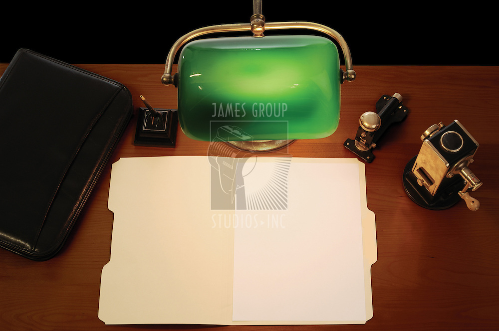 desktop with lamp, pen, briefcase, stapler, pencil sharpener and an open manila file folder with a blank letter-sized sheet of paper