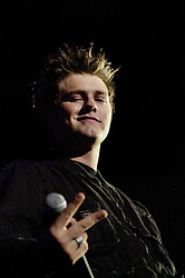 "Brian McFadden sticks two fingers up to the camera as Westlife play their third consecutive concert at the Hallam FM Arena at the start of their ""Unbreakable"" Tour 2003 Monday 21st July 2003<br /> <br /> Image Copyright Paul David Drabble<br /> 21 July 2003"