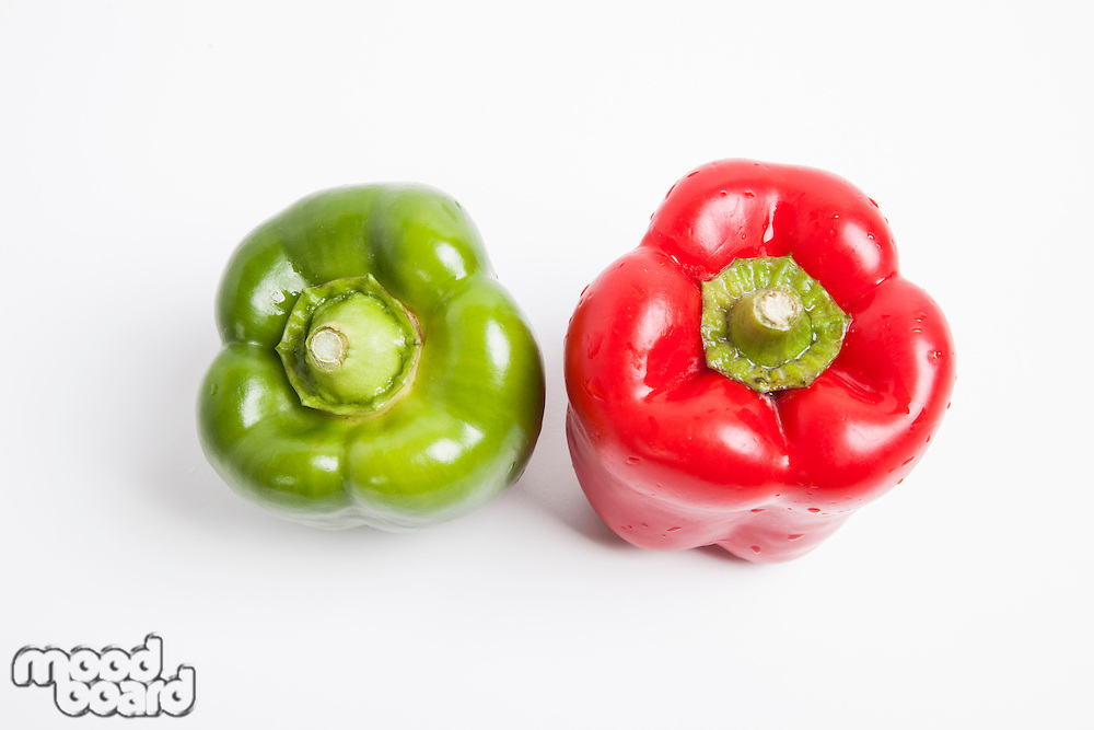 Top view of red and green fresh bell peppers over white background