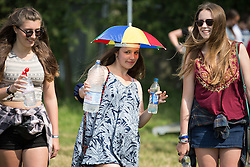 Image ©Licensed to i-Images Picture Agency. 18/07/2014  Henham Park , Suffolk, United Kingdom. A woman wearing an umbrella hat to keep cool as festival goers arrive at Henham Park on what is forecast to be the hottest day of the year so far with temperatures due to hit 30 degrees centigrade. The Latitude Festival of music and arts. Picture by Joel Goodman / i-Images