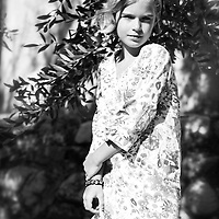 Young girl with blonde hair wearing summer dress looking at camera