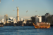 Bur Dubai. Dubai Creek. Abras (water taxis) and a tourist dhow in front of the skyline.