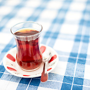 A glass of Turkish tea on a checkered blue and white tablecloth in Istanbul, Turkey. Turkish tea is traditionally served in small glasses shaped like this on a small plate. It is a black tea taken without milk but sometimes with beet sugar.