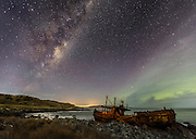 The Milky Way Galaxy ascends over the Olivia shipwreck near Bluff, at the southern tip of South Island, New Zealand.  The green glow of the Aurora Australis is from a mild & fading geomagnetic storm.