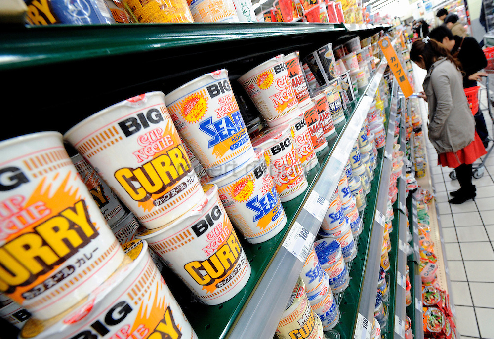 Shoppers browse through the hundreds of different instant noodle products on the shelves of a supermarket in Tokyo, Japan on 09 November 2008. .