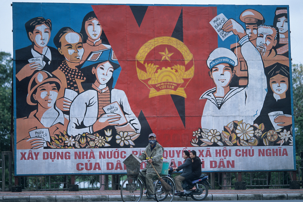 Asia, Vietnam, Hue, Traffic passes in front of Communist Party billboard along Perfume River