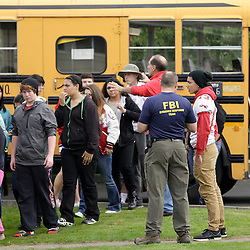 Students exit a bus with an FBI agent (R) speaking to students as they arrive at Shoultes Gospel Hall church after an active shooter situation at Marysville-Pilchuck High School in Marysville, Washington October 24, 2014. The shooter who opened fire at a high school in Washington State on Friday was a student at the campus and is now dead following the incident, police said.  REUTERS/Jason Redmond   (UNITED STATES)