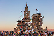 Robot Wedding at The Folly<br /> by: Dave Keane & The Folly Builders<br /> from: San Francisco, CA<br /> year: 2019<br /> <br /> The Folly represents an imaginary shantytown of funky climbable towers and old western storefronts, cobbled together from salvaged and reclaimed lumber from original San Francisco Victorians to be reborn in the desert, affording shelter, entertainment and perspective to the community.<br /> <br /> URL: www.thefollybrc.com<br /> Contact: info@thefollybrc.com<br /> <br /> https://burningman.org/event/brc/2019-art-installations/?yyyy=&artType=H#a2I0V000001AVkAUAW