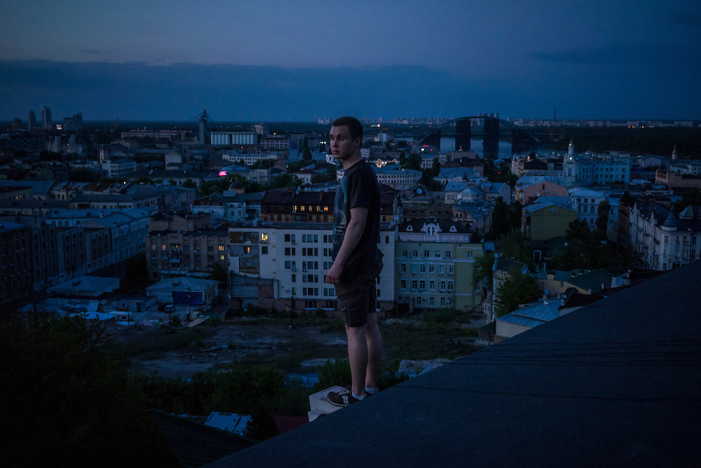 A man stands on the roof of an abandoned apartment building under construction at sunset in the Podil neighborhood on Monday, May 11, 2015 in Kyiv, Ukraine.