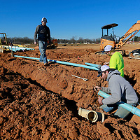 Thomas Wells | BUY AT PHOTOS.DJOURNAL.COM<br /> Tyler Dowdy, left, walk over to check in on th progress being made by Chris Taylor and Hunter Highfield as they assemble the main water line that will feed the new baseball fields under contruction in Corinth on Wednesday on Droke Road.