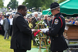 Bardstown mayor Bill Sheckles, right, accepts a Bardstown flag from Louisville Metro Police Honor Guard officer Kris Pedigo before presenting it to the Ellis family, Thursday, May 30, 2013 at High View Cemetery in Chaplin. Photo by Jonathan Palmer