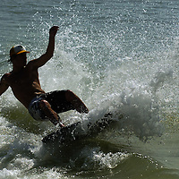 (02.02.2005)(PHOTO/CHIP LITHERLAND) -- Scott Romeo, 18, of Bradenton skims a wave at Holmes Beach, Florida, on Anna Maria Island Wednesday morning.