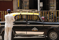 A man cleaning his Taxicab in Colaba, Mumbai, India