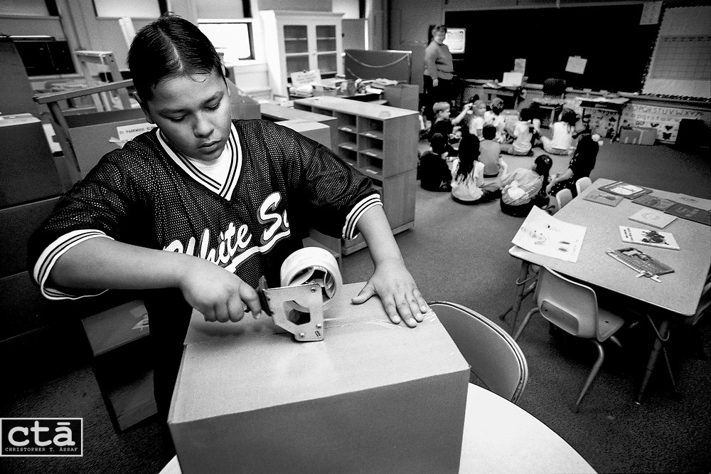 Sixth-grader Joey Lawrence tapes packed boxes in Kay Flores' kindergarten classroom as she gathers her students to watch a video. The materials will be shipped to Flores' new teaching assignment.