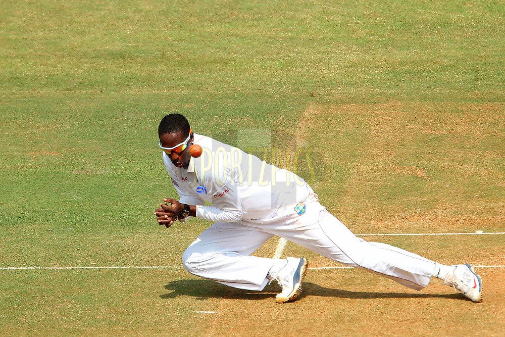 Shane Shillingford of West Indies fields from his own bowling during day two of the second Star Sports test match between India and The West Indies held at The Wankhede Stadium in Mumbai, India on the 15th November 2013<br /> <br /> This test match is the 200th test match for Sachin Tendulkar and his last for India.  After a career spanning more than 24yrs Sachin is retiring from cricket and this test match is his last appearance on the field of play.<br /> <br /> <br /> Photo by: Ron Gaunt - BCCI - SPORTZPICS<br /> <br /> Use of this image is subject to the terms and conditions as outlined by the BCCI. These terms can be found by following this link:<br /> <br /> http://sportzpics.photoshelter.com/gallery/BCCI-Image-Terms/G0000ahUVIIEBQ84/C0000whs75.ajndY