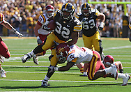 September 11 2010: Iowa Hawkeyes running back Adam Robinson (32) tries to pull away from Iowa State Cyclones cornerback Jeremy Reeves (5) during a run in the first half of the NCAA football game between the Iowa State Cyclones and the Iowa Hawkeyes at Kinnick Stadium in Iowa City, Iowa on Saturday September 11, 2010. Iowa defeated Iowa State 35-7.