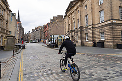 Cyclist on an empty Royal Mile  during the coronavirus lockdown in Edinburgh Old Town, Scotland, UK