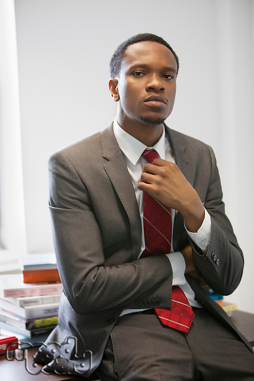 Portrait of a confident young businessman sitting on desk