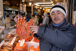 Stallholder displaying large red crab at fish market in Sapporo Hokkaido Island in Japan