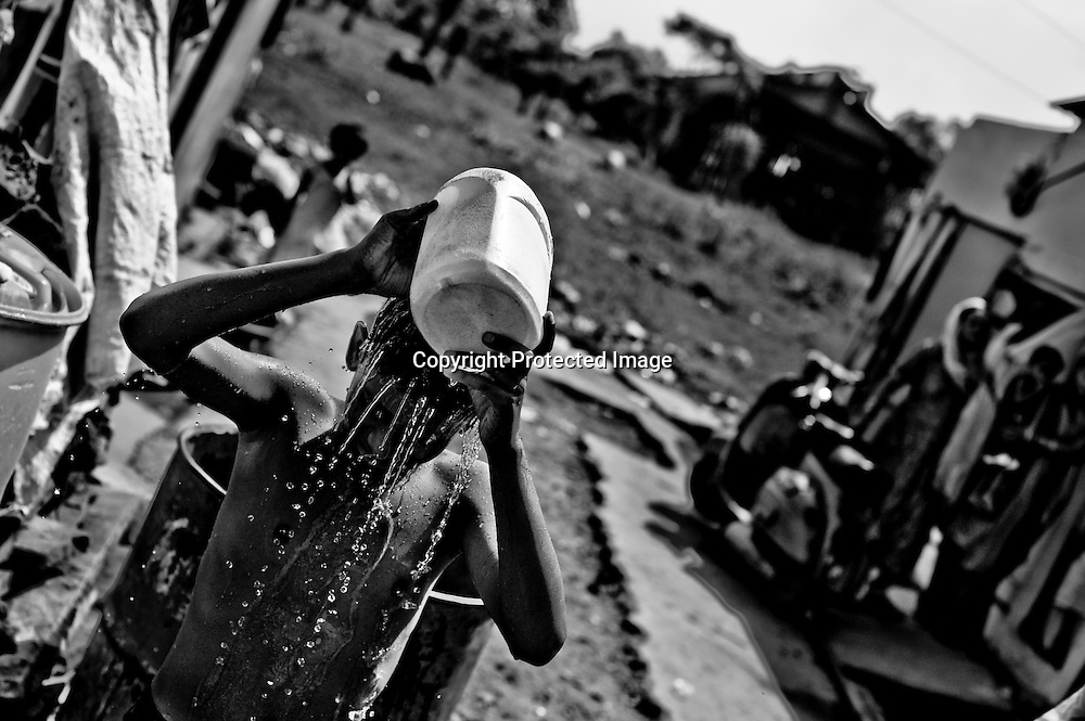 Bhopal, twenty-five years later..A boy bathes with site of the Union Carbide plant behind him in the city of Bhopal in the state Madhya Pradesh, India, October 10, 2009. ..Twenty-five years after a gas leak in the Union Carbide factory in Bhopal killed at least eight thousand people, toxic material from the 'biggest industrial disaster in history' continues to affect Bhopalis. A new generation is growing up sick, disabled and struggling for justice...The effects of the disaster on the health of generations to come, both through genetics transferred from gas victims to their children and through the ongoing severe contamination, caused by the Union Carbide factory, has only started to develop visible forms recently...