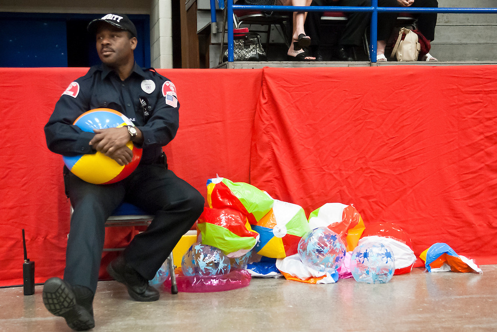 Lathan Goumas | MLive.com..A security officer deflates beach balls that have been confiscated from graduates during the 2012 Swartz Creek High School commencement ceremony at the Perani Arena in Flint, Mich. on Tuesday June 12, 2012.