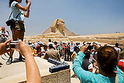 Tourists look for prime positions to photograph the Great Sphinx and Cheops Pyramid at Giza, near Cairo, Egypt. The Sphinx and the Great Pyramid of Cheops are thought to have been built in around 2600 BC. Carved out of the surrounding limestone bedrock, the Great Sphinx is a statue with the face of a man and the body of a lion; he faces due east and sits with a small temple between his paws.