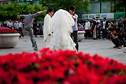 Couple getting photographed after their wedding on a public square in the center of Beijing. Beijing is the capital of the People's Republic of China and one of the most populous cities in the world with a population of 19,612,368 as of 2010.
