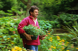 Alan Titchmarsh carrying plants ready for planting out in the garden