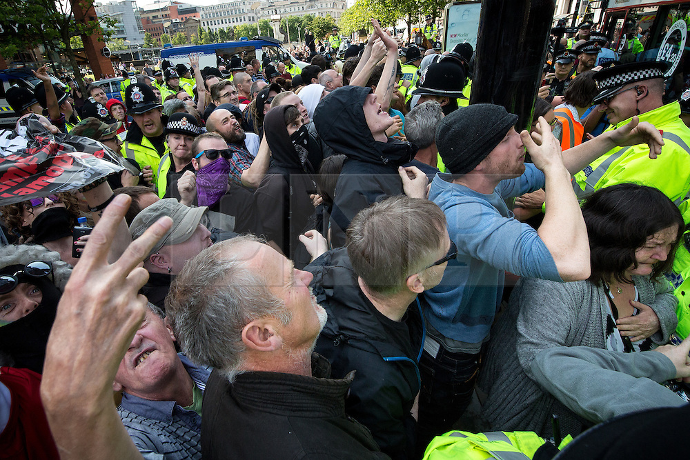 """© Licensed to London News Pictures . 22/08/2015 . Manchester , UK . Anti-fascists surge forwards as demonstrators are driven away on a coach . Far-right nationalist group , """" North West Infidels """" and Islamophobic , anti-Semitic and white supremacist supporters , hold a rally in Manchester City Centre . Photo credit : Joel Goodman/LNP"""