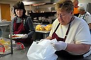 25 MARCH 2011 -- LEMAY, Mo. -- Peggy Von Der Haar (right) packs a carry-out order while Debra Dufour prepares a plate for a diner eating in the dining room during the fish fry at St. Andrew Catholic Church in Lemay, Mo. Friday, March 25, 2011. Volunteers served more than 600 meals Friday and ran out of the parish's signature macaroni and cheese, said Karen Wood, one of the parishioners who helps organize the fish fry. Image © copyright 2011 Sid Hastings.