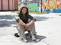 Young man sitting on skateboard outdoors portrait