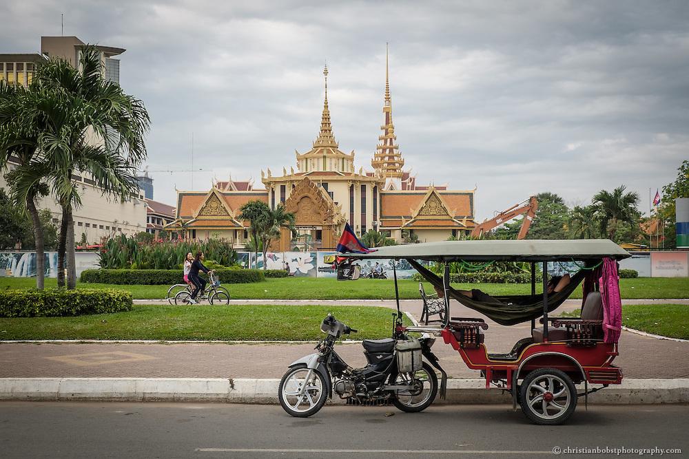 Ein Tuk Tuk Fahrer schläft morgens in einer Hängematte in seinem Tuk Tuk beim Chea Sim Park  in Phnom Penh. Im Hintergrund sieht man das Gebäude des Supreme Courts.