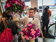"27 MARCH 2015 - BANGKOK, THAILAND:  A delivery man brings flowers into a store in the ""EmQuartier,"" a new mall in Bangkok. ""EmQuartier"" is across Sukhumvit Rd from Emporium. Both malls have the same corporate owner, The Mall Group, which reportedly spent 20Billion Thai Baht (about $600 million US) on the new mall and renovating the existing Emporium. EmQuartier and Emporium have about 450,000 square meters of retail, several hotels, numerous restaurants, movie theaters and the largest man made waterfall in Southeast Asia. EmQuartier celebrated its grand opening Friday, March 27.   PHOTO BY JACK KURTZ"
