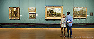 Couple viewing The Hay Wain painting by English painter John Constable in the Sackler room of the National Gallery in London. Photographed for Visit Britain as part of their 2013 culture campaign. THIS IMAGE IS COPYRIGHT VISIT BRITAIN.