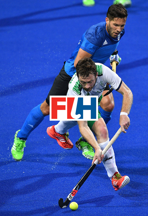 Argentina's Agustin Mazzilli and Ireland's John Jackson (front) vie during the mens's field hockey Ireland vs Argentina match of the Rio 2016 Olympics Games at the Olympic Hockey Centre in Rio de Janeiro on August, 12 2016. / AFP / Carl DE SOUZA        (Photo credit should read CARL DE SOUZA/AFP/Getty Images)
