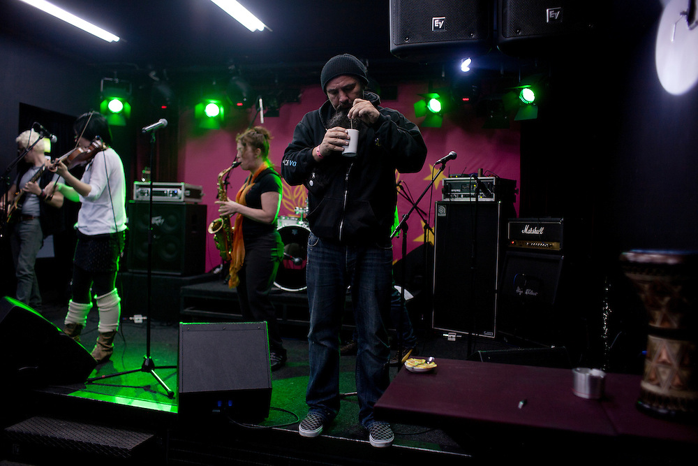 "Srdjan ""Gino"" Jevdjevic, center, has a cup of tea on stage during Kultur Shock's soundcheck at DFK Club in Banja Luka in an effort to sooth his ailing voice on the second day of their tour..."