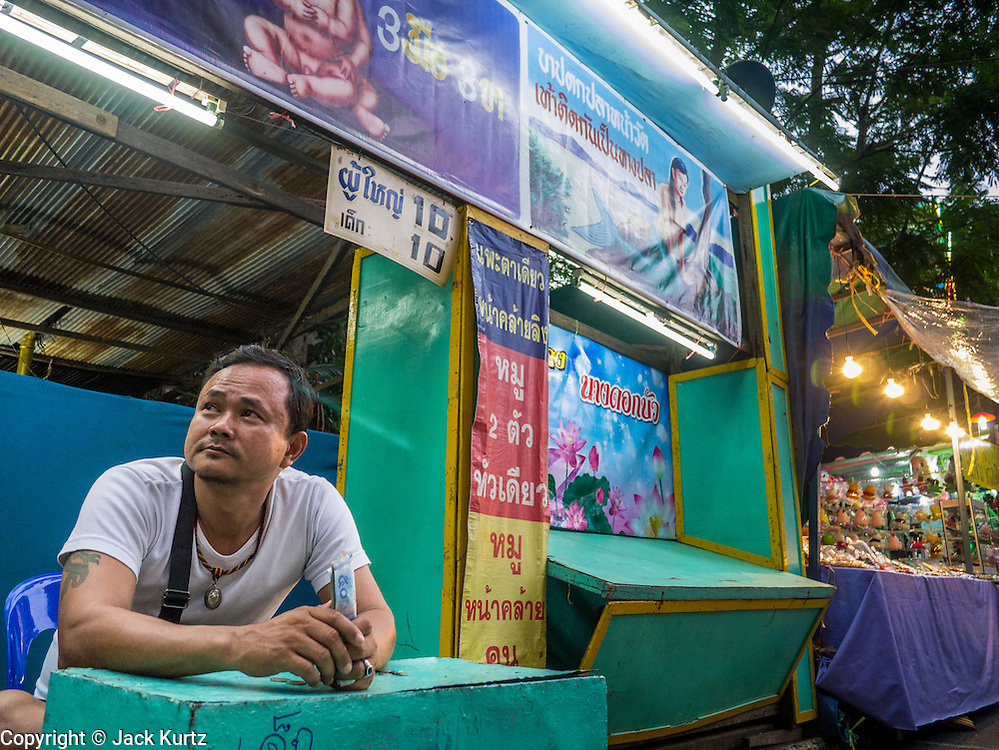"""27 NOVEMBER 2012 - BANGKOK, THAILAND:  A """"freak show"""" ticket taker at the Wat Saket Temple Fair in Bangkok. Wat Saket, popularly known as the Golden Mount or """"Phu Khao Thong,"""" is one of the most popular and oldest Buddhist temples in Bangkok. It dates to the Ayutthaya period (roughly 1350-1767 AD) and was renovated extensively when the Siamese fled Ayutthaya and established their new capitol in Bangkok. The temple holds an annual fair in November, the week of the full moon. It's one of the most popular temple fairs in Bangkok. The fair draws people from across Bangkok and spills out in the streets around the temple.   PHOTO BY JACK KURTZ"""